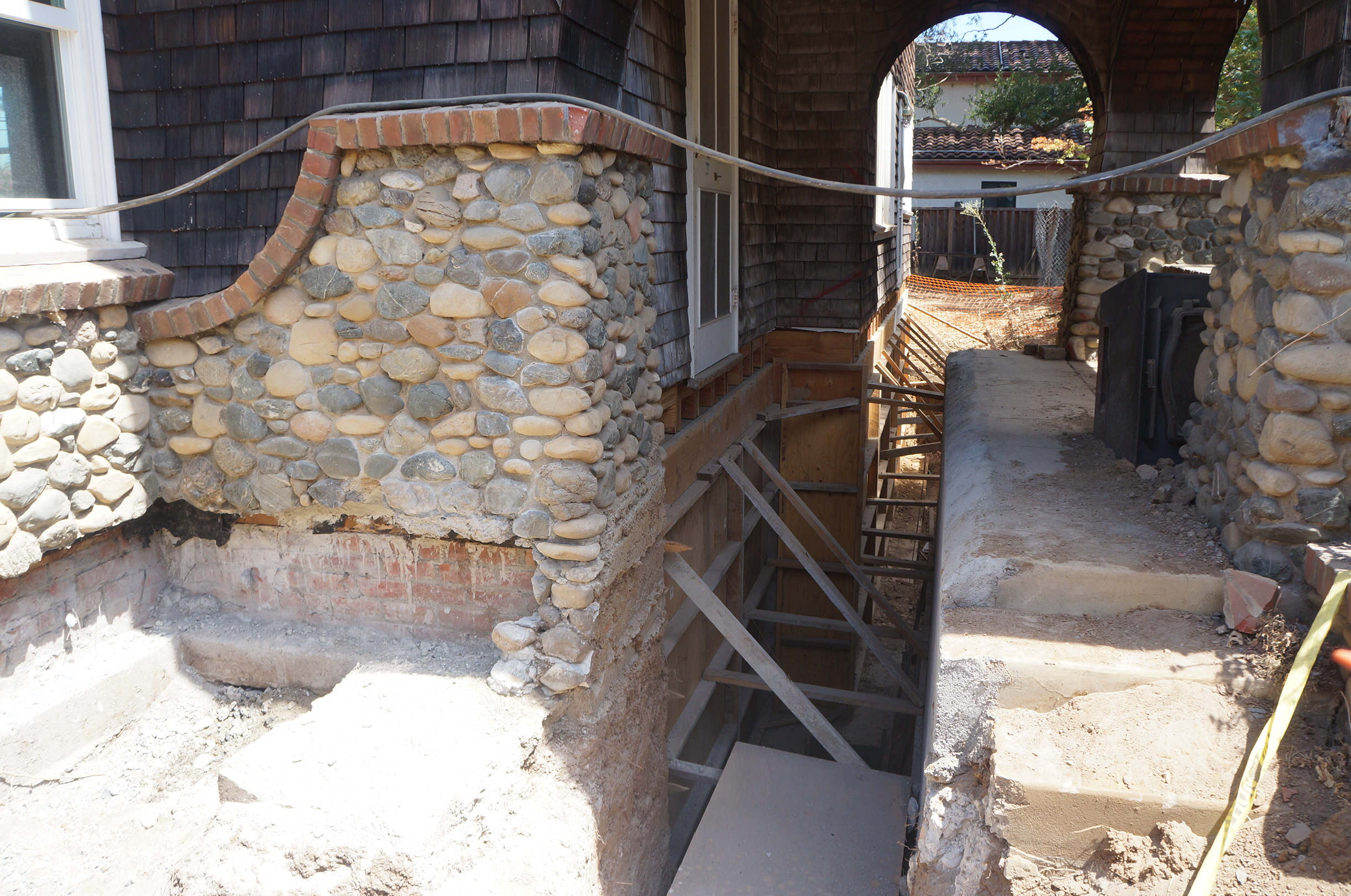 Details of the west façade during construction: the river rock has been salvaged and the concrete porch area excavated for new foundations.